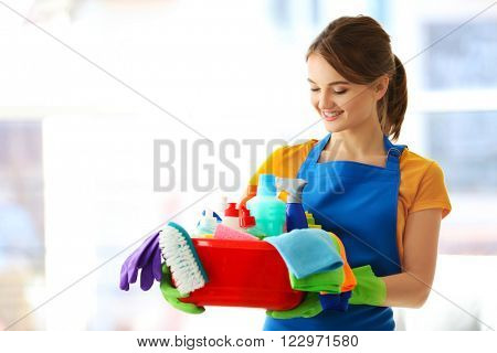 Cleaning concept. Young woman holds plastic basin with washing fluids and rags in hands