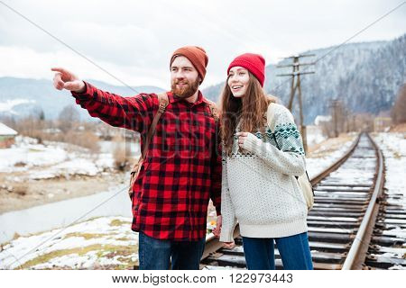 Happy attractive bearded young man standing on railway and showing direction to his girlfriend