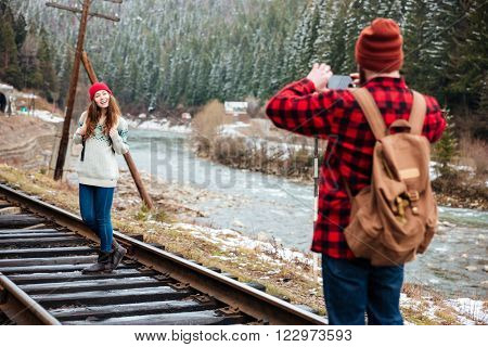 Young man with backpack taking photos of his girlfriend on old railway track in mountains