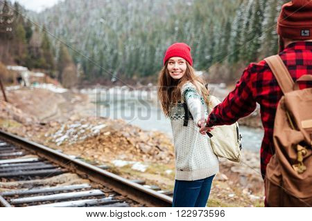 Happy young couple with backpacks holding hands and walking along railway in mountains