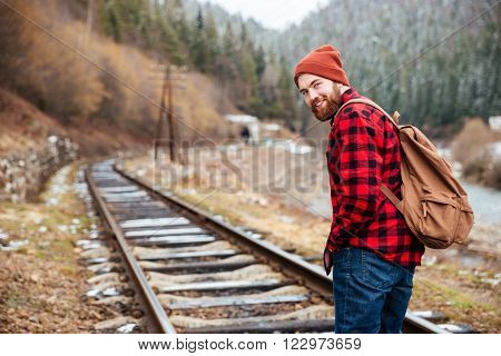 Cheerful attractive bearded young man with backpack walking along railroad in mountains