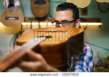 Lute maker shop and classic music instruments: young adult artisan fixing old classic guitar. The man looks carefully at bridge and arm to check the wood curvature