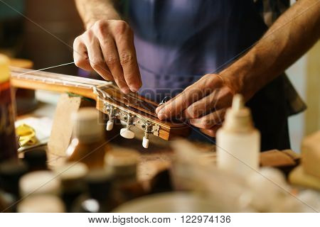 Lute maker shop and classic music instruments: young adult artisan fixing old classic guitar adding a cord and tuning the instrument. Close up of hands and palette