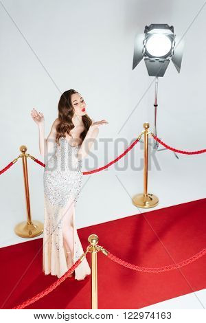 Full length portrait of a cute woman posing on red carpet and blowing kiss