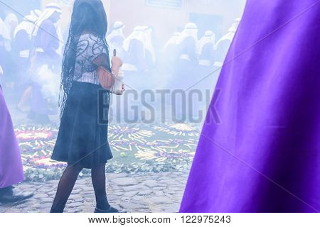 Antigua Guatemala - March 20 2016: Girl walks through incense smoke with float bearers called cucuruchos in Palm Sunday procession in colonial town with most famous Holy Week celebrations in Latin America.