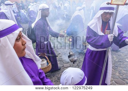 Antigua Guatemala - March 20 2016: Float bearers called cucuruchos cleanse air with incense smoke in Palm Sunday procession in colonial town with most famous Holy Week celebrations in Latin America.