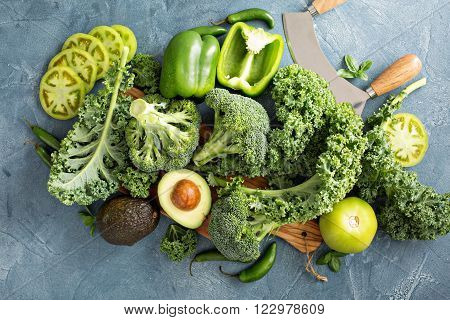 Variety of green vegetables on the table including kale, broccoli and avocado