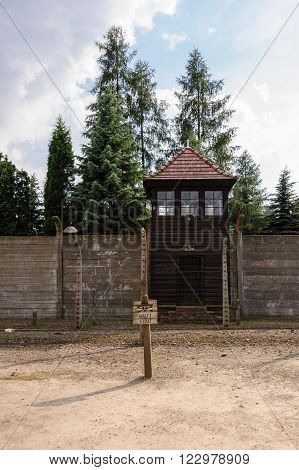 Auschwitz I - Birkenau concrete wall erected between the outer fence posts and watch tower to block visibility from the outside looking inside the camp.