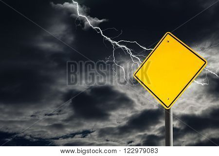 An empty traffic sign against a dark cloudy and thunderous sky. Conceptually warning of danger ahead. Blank sign for copy space and message.