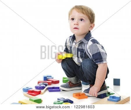 An adorable toddler boy looking up and squatting as he's surrounded by wooden blocks and a stack toy.  On a white background.