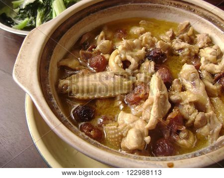 Chinese chicken stew with longan pulp in clay pot with broth.