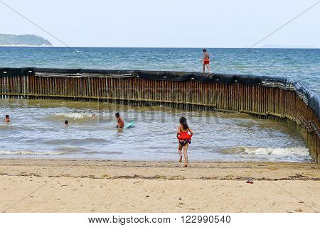 Townsville, Australia January 15, 2011: Children play in and on swimming enclosure at beach on hot summer day