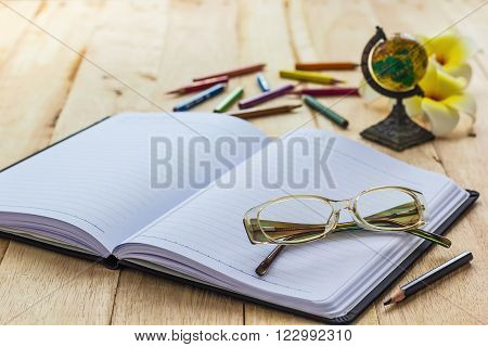 a photo of glasses on notebook,a photo of glasses on notebook