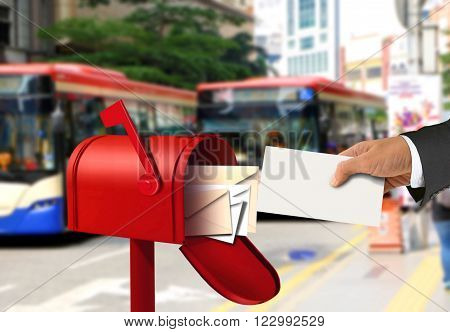 Hand taking a letter from a red postal box