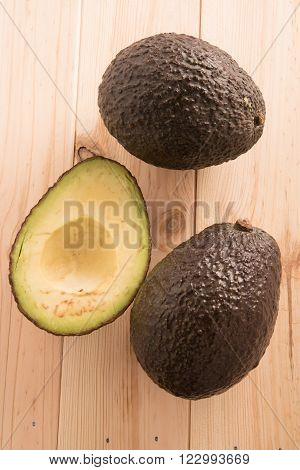 two  and half Avocados on wooden background