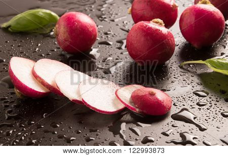 fresh radish  and basil in a wet background