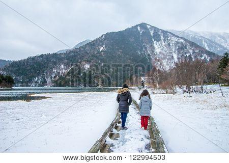 Nikko Japan - Dec 04 2015: Girls in winter clothes walking towards a mountain in snow on a lakeside boardwalk or bridge covered with snow. Taken at Lake Yuno Yumoto Nikko Japan.