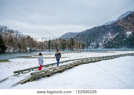 Nikko Japan - Dec 04 2015: Girls in winter clothes walking one after the other on a lakeside boardwalk or bridge covered with snow. Taken at Lake Yuno Yumoto Nikko Japan.
