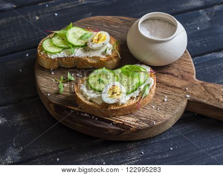 Healthy delicious breakfast or snack - open sandwich with goat's cheese and cucumber and boiled quail eggs