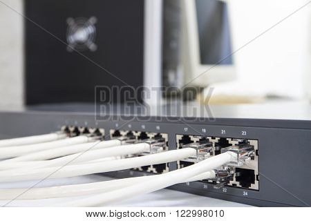 Lan network switch with ethernet cables plugged in on computer background