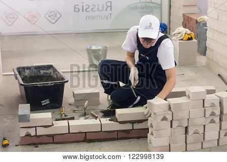 Tyumen, Russia - March 23. 2016: Open championship of professional skill among youth. Worlld skills Russia Tyumen - 2016. Young bricklayer performs a task of competition of professionals