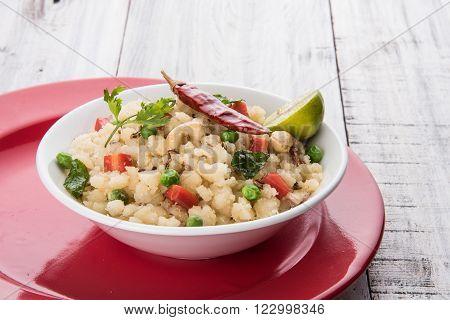 Rava Upma - Popular south Indian breakfast wiih semolina and vegetables, selective focus, Upma or upama is a South Indian breakfast, cooked from dry roasted semolina. seasonings of vegetables