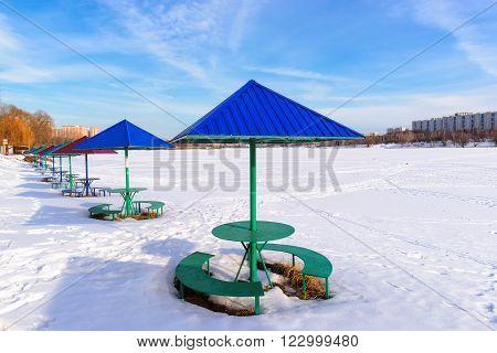 Snow beach with beach umbrellas in winter.