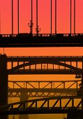 Telephoto view of Newcastle/Gateshead bridges overlaid with red/orange color for effect.