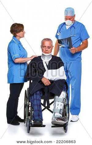 Photo of a doctor in scrubs examining an x-ray of the man in the wheelchairs hand, nurse standing to the side, isolated on a white background.