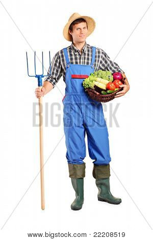 Full length portrait of a male farmer holding a pitchfork and bucket with vegetables isolated on white background