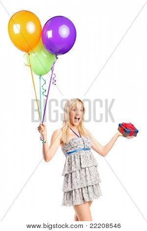 An attractive woman holding balloons and a gift isolated on white background