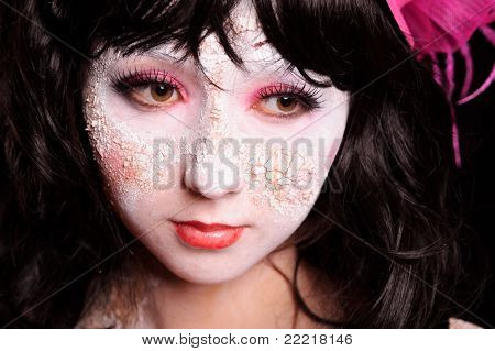 brunette woman with unusual make-up and cracks on skin, may be use for old doll concept