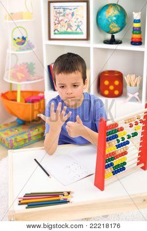 Little boy preparing for elementary school doing simple math exercises