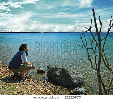 A man absorbed in thought on the bank of a lake. The unique keyword for this collection is: lake77