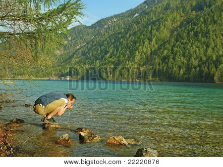 a man is drinking water from a clean lake. The unique keyword for this collection is: lake77