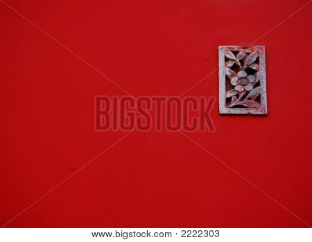Red Wall With Stone Carving Of Flower