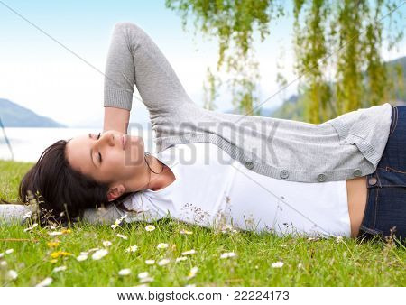 young woman lying in a meadow in front of a lake