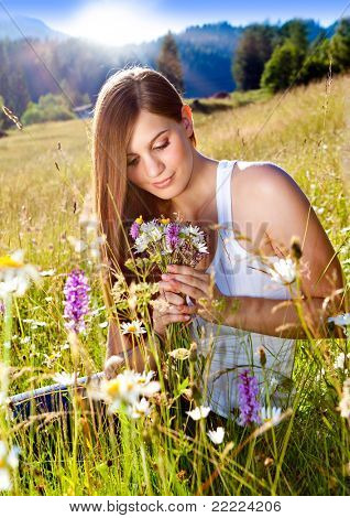 beautiful young girl sitting in a sunset marguerite meadow