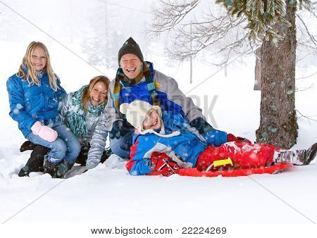 young funny family with sledge under a tree in winter-landscape