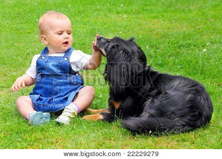 Little girl and here dog on a grass.