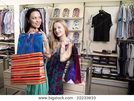 Two Stylish Women With Paperbags Meet In Mall