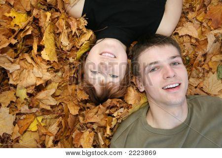 Young Couple Lies On Yellow Leaves