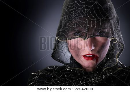 A portrait of a hooded female vampire standing against dark background