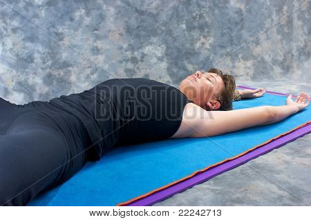 Young Athletic Woman Stretched Out On Yoga Mat