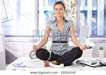 Young office worker meditating on top of desk in bright office.?