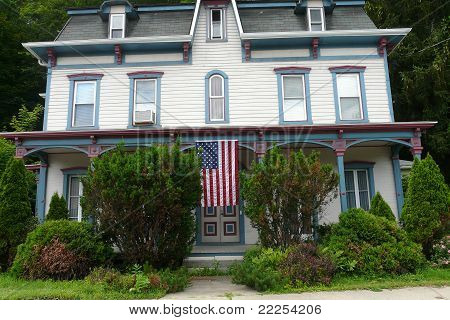 american flag hanging on victorian house