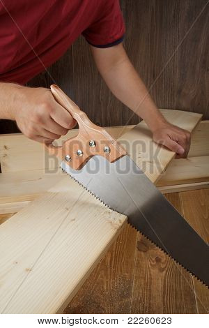 Wood workshop. Carpenter cutting plank with hand saw.