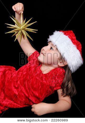 Little Girl Laying On Ground Holding Golden Chritsmas Ornament