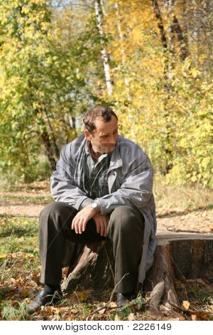 Elderly Man Sits In The Park In Autumn