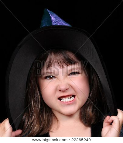 Close-up Of Sweet Little Girl In Witches Hat Making A Scary Face